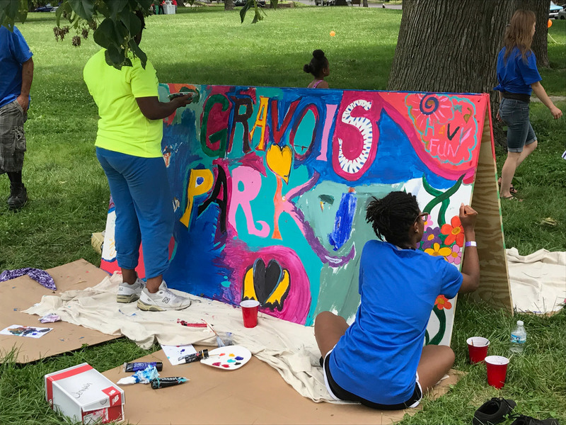 Volunteers paint a sign at Gravois Park