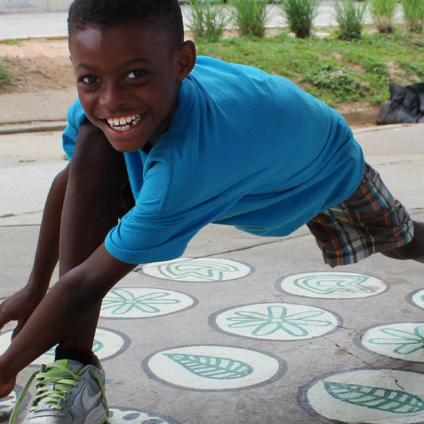 Smiling boy plays on painted asphalt