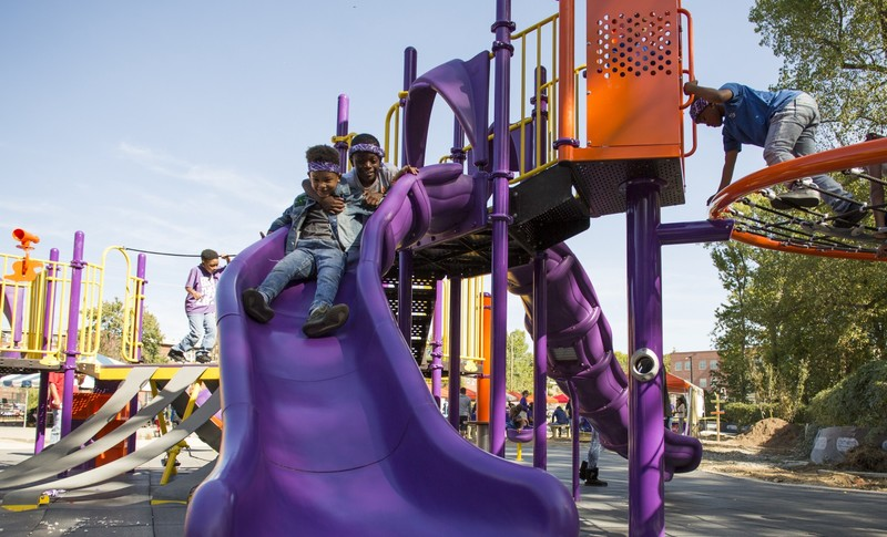 Kids slide down a purple slide