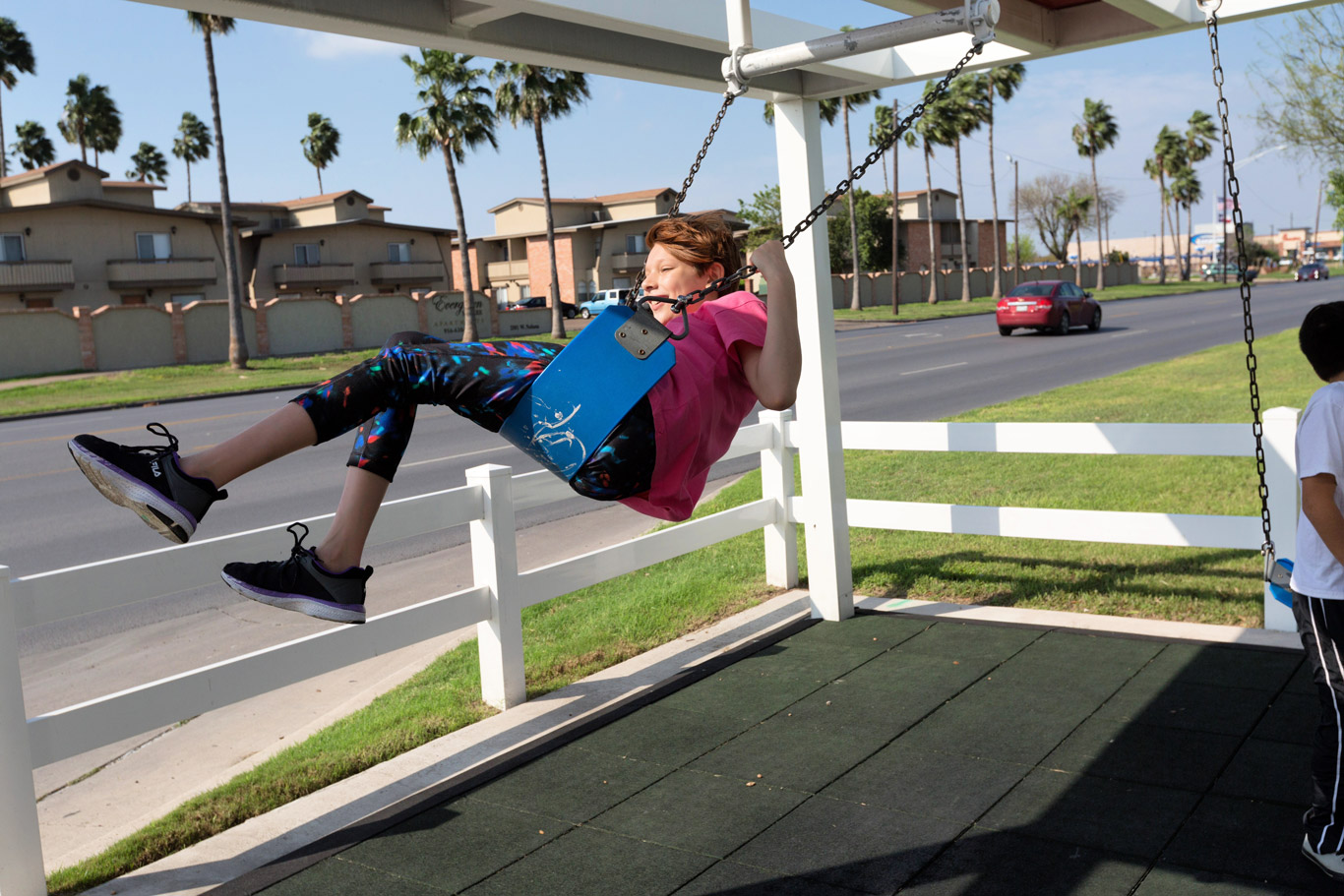 Kid swings at a bus stop that also has a swingset