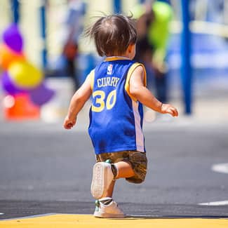 A young boy runs across the court in a Stephen Curry jersey
